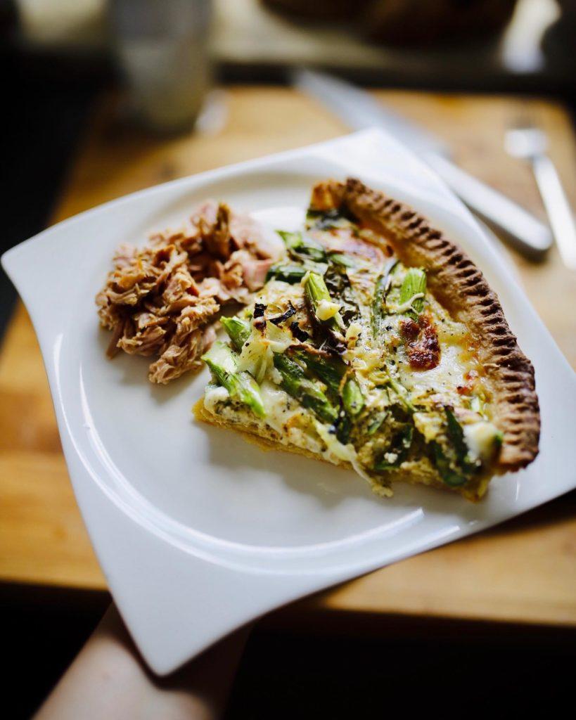 Kawałek zielonej tarty ze szparagami podany z tuńczykiem w oliwie.